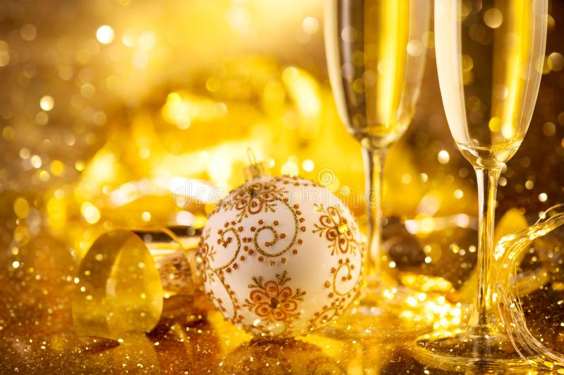 Holiday Champagne Flute over Golden glow background. Christmas and New Year celebration. Two Flutes with Sparkling Wine. Over Holiday Bokeh Blinking Background stock image