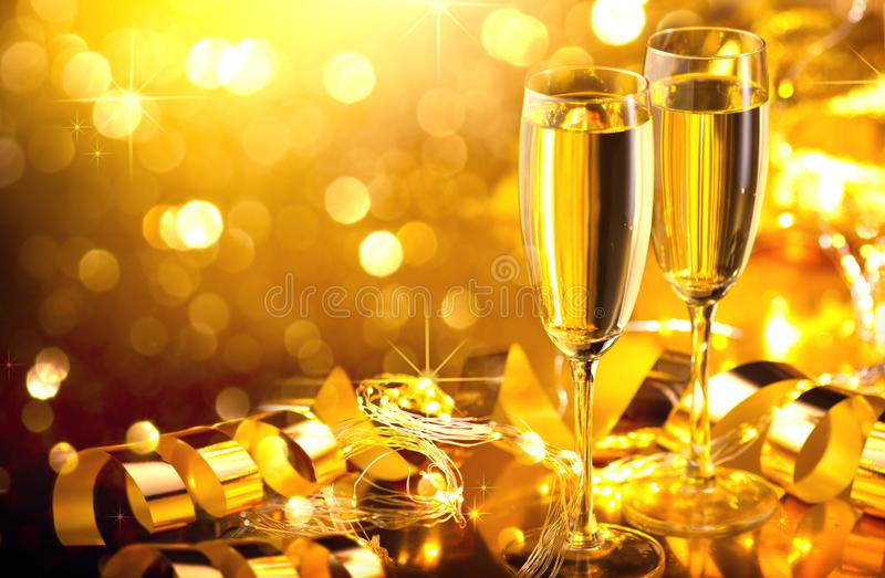 Holiday Champagne Flute over Golden glow background. Christmas and New Year celebration. Two Flutes with Sparkling Wine. Over Holiday Bokeh Blinking Background royalty free stock photo
