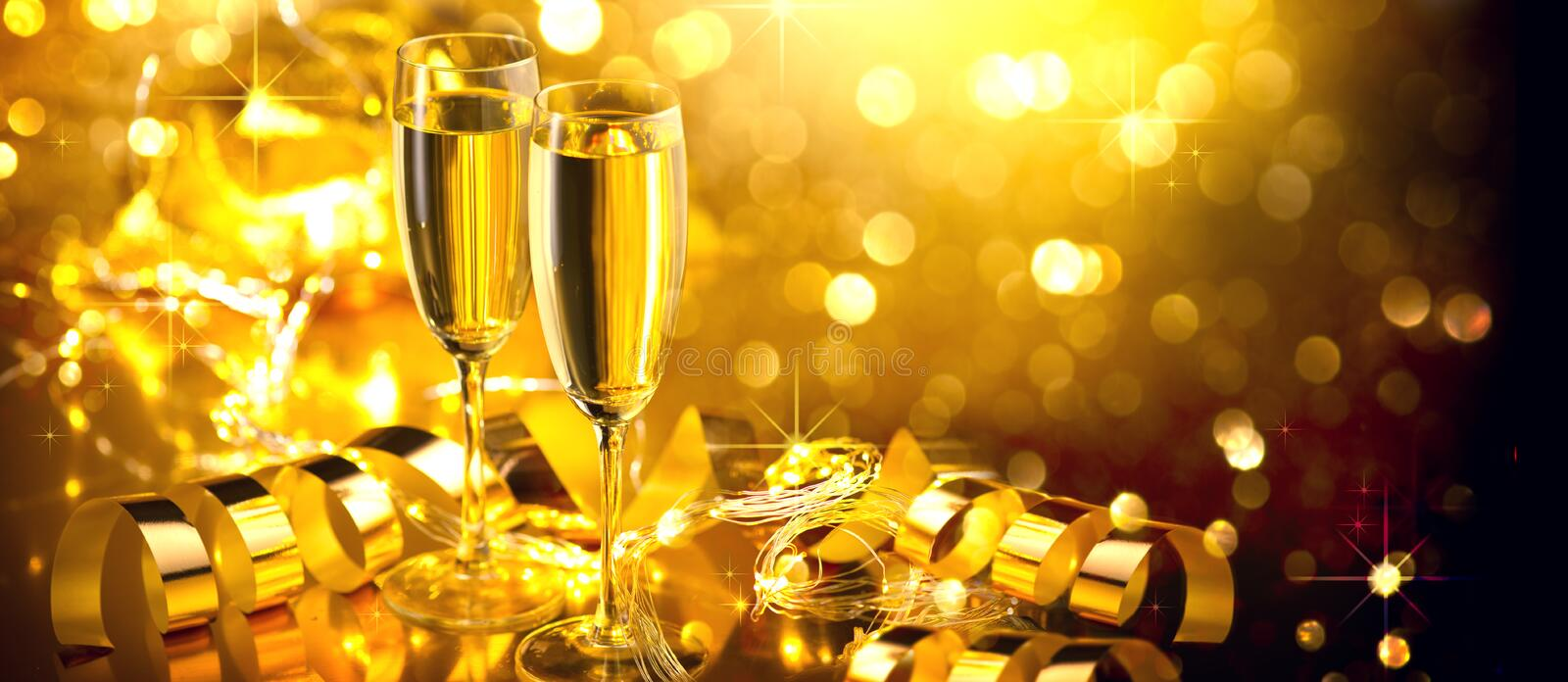 Holiday Champagne Flute over Golden glow background. Christmas and New Year celebration. Two Flutes with Sparkling Wine. Over Holiday Bokeh Blinking Background stock photos