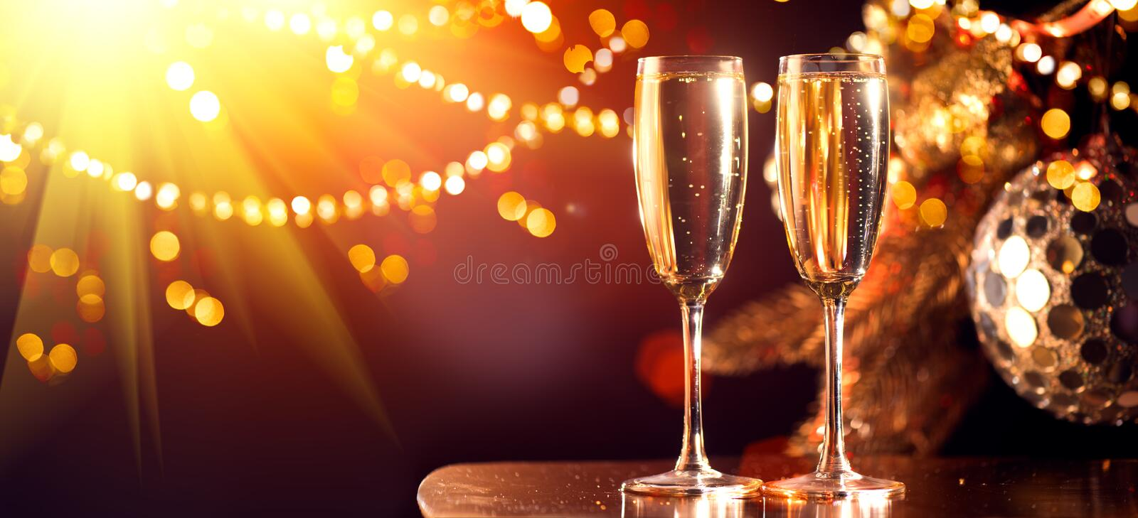 Holiday Champagne Flute over Golden glow background. Christmas and New Year celebration. Two Flutes with Sparkling Wine royalty free stock images