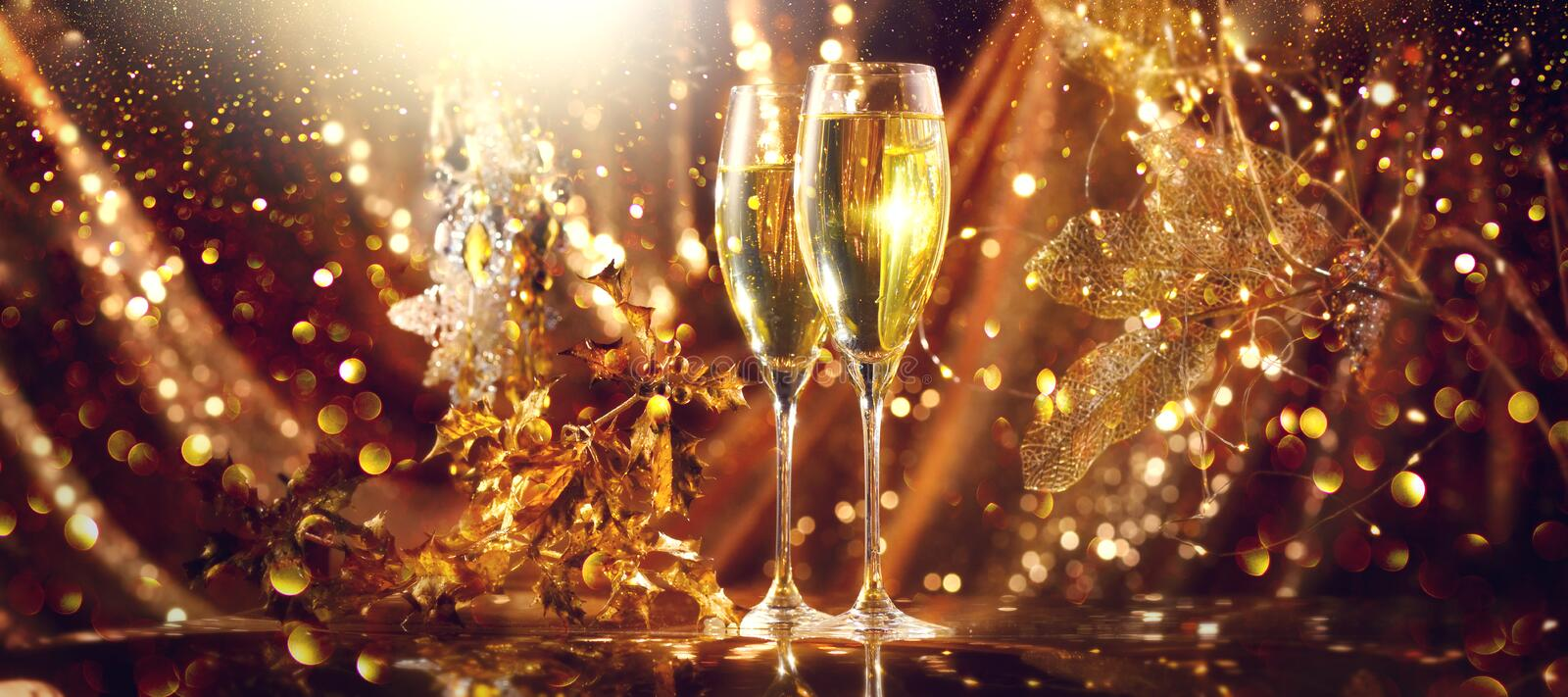 Holiday Champagne Flute over Golden glowing background. Christmas and New Year celebration. Two Flutes with Sparkling Wine stock photography