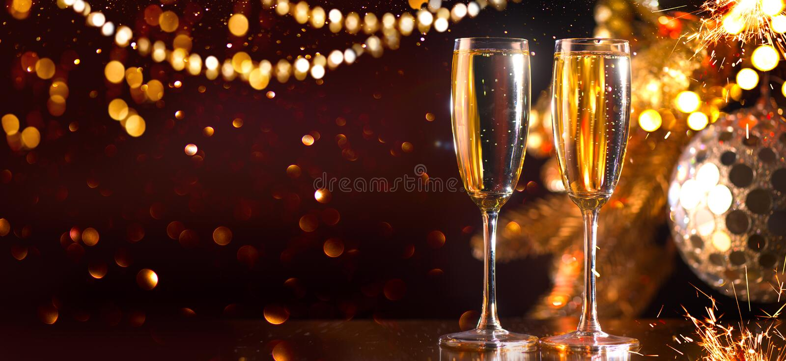Holiday Champagne Flute over Golden glowing background. Christmas and New Year celebration. Two Flutes with Sparkling Wine royalty free stock photo