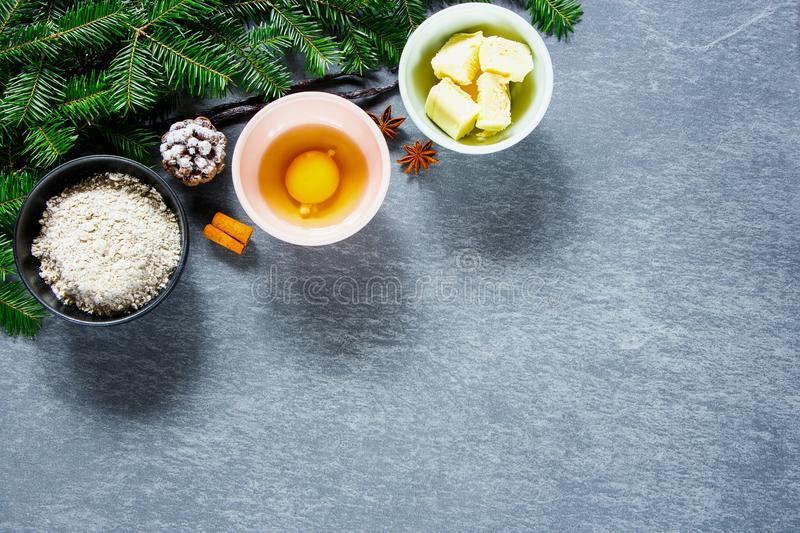 Holiday Christmas baking. Holiday time. Christmas cooking and baking ingredients. Dough ingredients and decorations on vintage stone background. Top view stock image