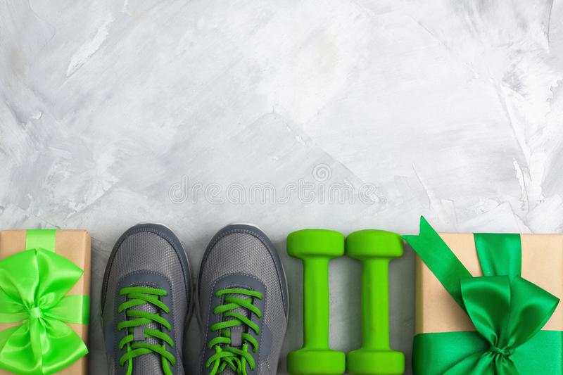 Holiday christmas birthday party sport flat lay composition. With gray shoes, green dumbbells and craft gifts with green bow on gray concrete background. Top royalty free stock photo