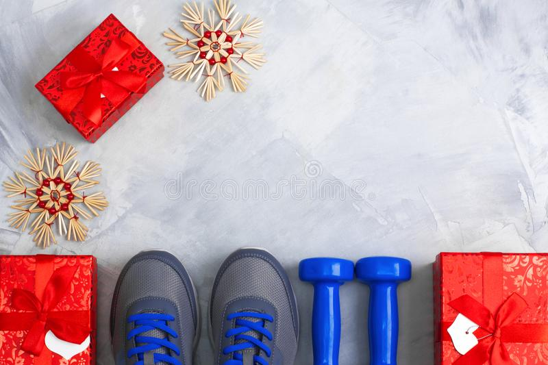 Holiday christmas birthday party sport flat lay composition. With gray shoes, blue dumbbells and red gifts on gray concrete background. Top view, horizontal royalty free stock photos