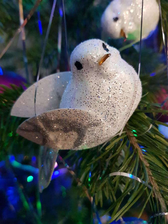 Holiday christmas decoration in retro style, glitter and tinsel. Beautiful close-up of white bird. Happy new year design royalty free stock image