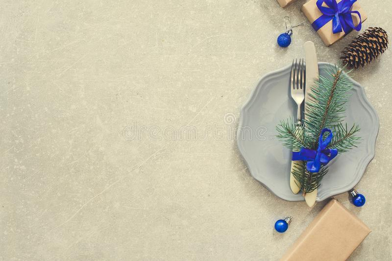 Holiday Christmas food background, cutlery, plate and Christmas. Tree branch, gifts on a stone background royalty free stock photo