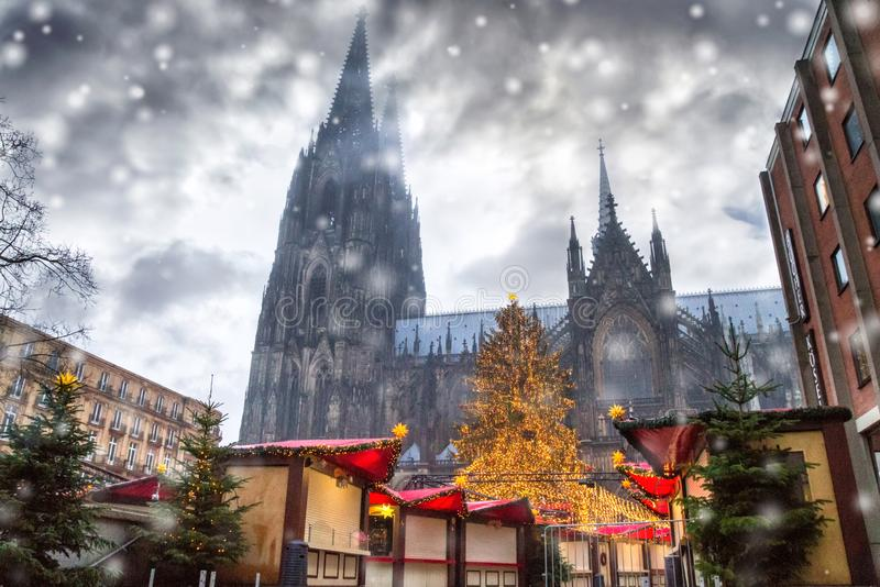 Holiday cityscape - view of the Christmas Market Weihnachtsmarkt early morning on background the Cologne Cathedral royalty free stock photography