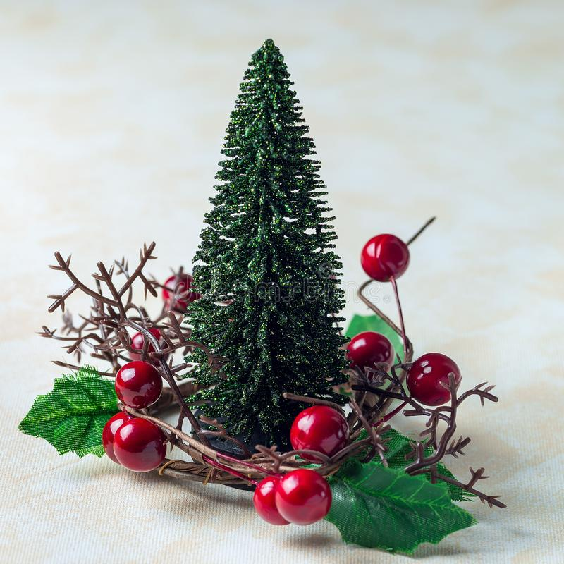 Holiday composition with christmas tree and wreath with holly berries, on white beige background, square format. Holiday composition with christmas tree and stock image