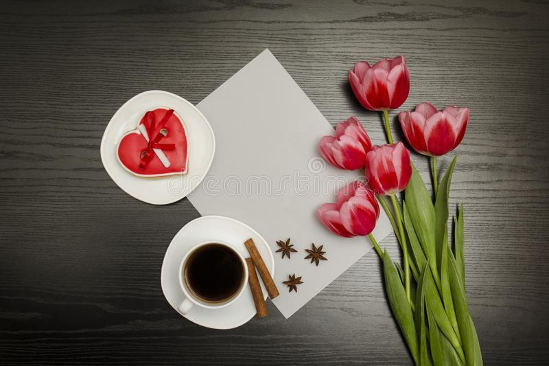 Holiday concept. Bouquet of pink tulips, a cup of coffee, red heart-shaped cookies with a note, a piece of paper on a black wooden royalty free stock photos