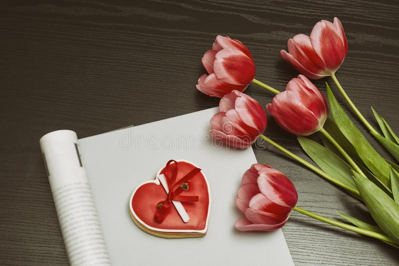 Holiday concept. Bouquet of pink tulips, red heart-shaped cookies with a note, empty magazine on a black wooden background. royalty free stock images