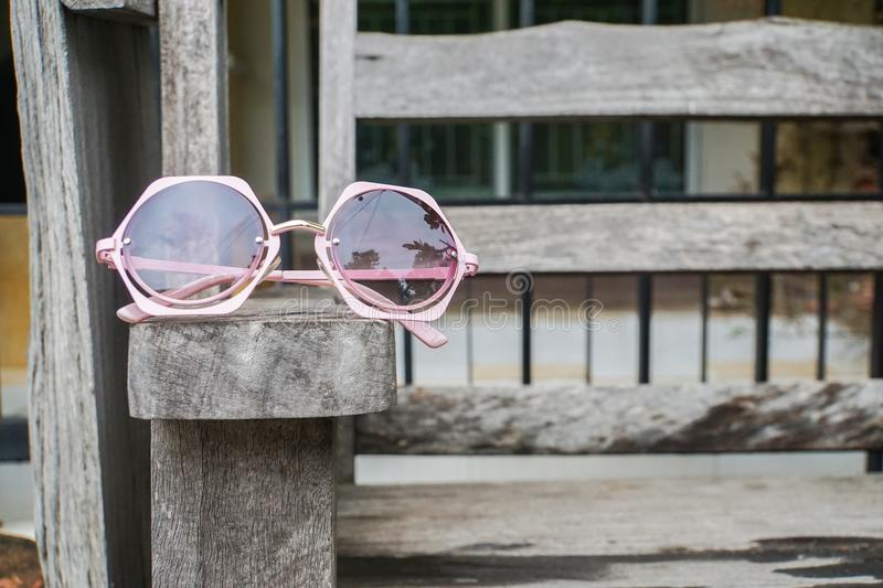 Cute pink women sunglasses on wooden bench stock image