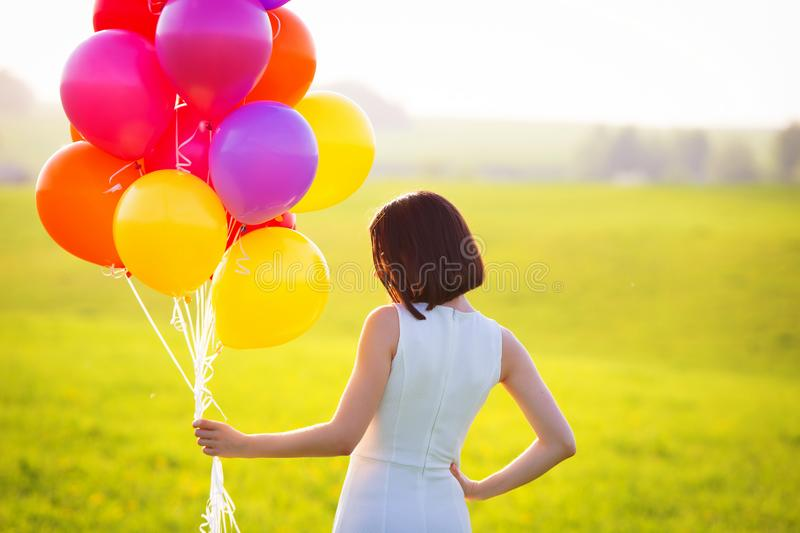 Holiday concept. Girl in white dress holding colorful air balloons. Portrait of young woman outdoors on green summer field. royalty free stock image