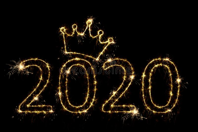 Holiday concept. Number 2020 with crown decor written sparkling sparklers isolated on black background. Overlay templatefor for stock photo