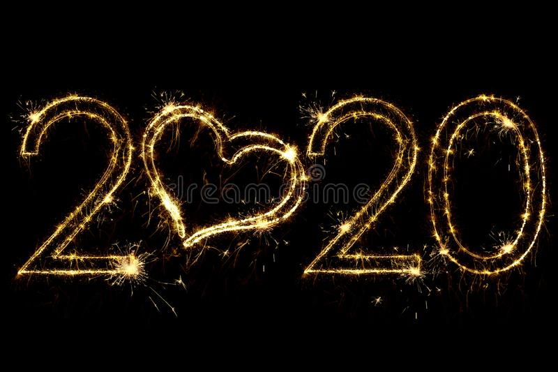 Holiday concept. Number 2020 with heart decor written sparkling sparklers isolated on black background. Overlay templatefor for stock photos