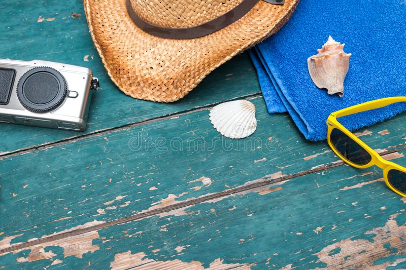 Holiday Concept: Vintage wood table with holiday accessories: Straw hat, sunglasses, shells, vintage camera and bath towel. Summer background: Concept of leisure stock photography