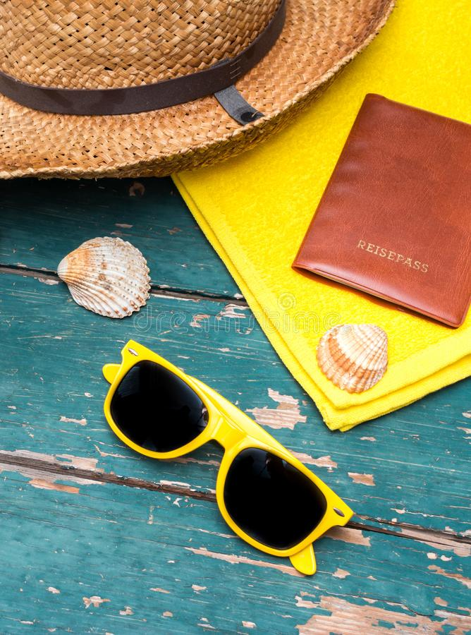 Holiday Concept: Vintage wood table with holiday accessories: Straw hat, sunglasses, shells, vintage camera and bath towel. Summer background: Concept of leisure stock photo