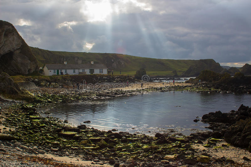 Holiday cottages at Ballintoy harbor on the North Antrim Coast of Ireland with its stone built boathouse on a day in spring stock photos