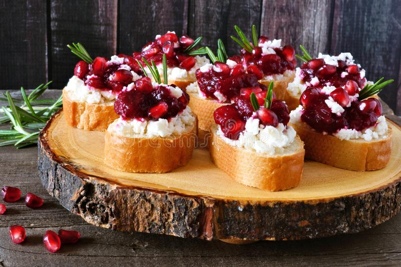 Holiday crostini appetizers with cranberries, pomegranates and feta on a wood log platter stock images