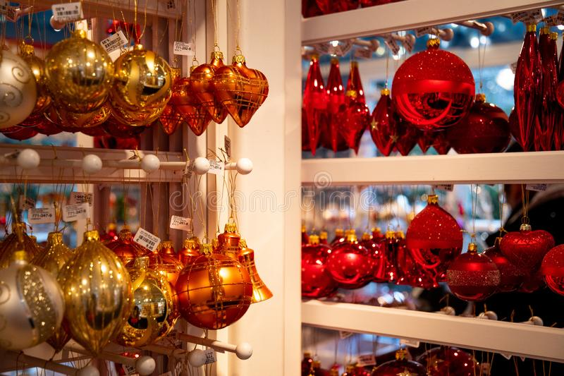 Golden and red glass bulbs Christmas ornaments are hanging on shelves at Christmas market in Berlin Germany. royalty free stock image
