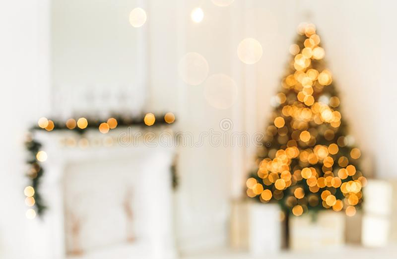 Holiday decorated room with Christmas tree and decoration, background with blurred, sparking, glowing light. royalty free stock photos