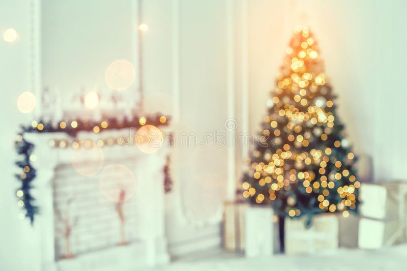 Holiday decorated room with Christmas tree and decoration, background with blurred, sparking, glowing light. stock photo