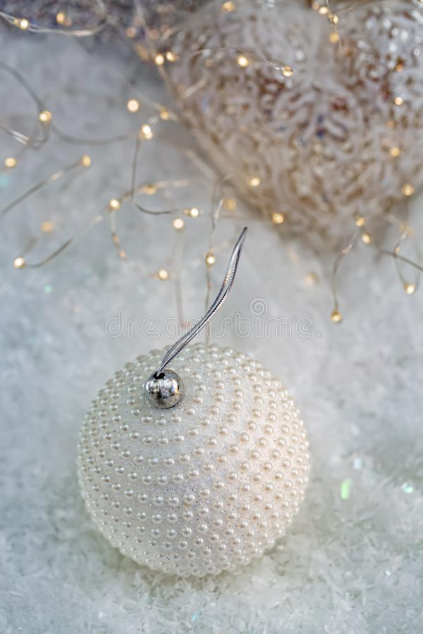 Christmas decoration. White ball nacre pearls on a snow and beautiful blurred background of glittering bokeh with glowing lights. stock photos