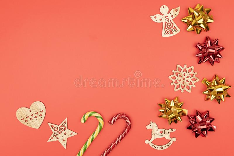 Holiday decorations. Frame made of red and gold bows, wooden Christmas tree toys, candy canes on red background. top stock image