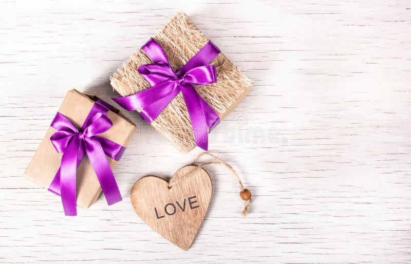 Holiday decorations with gift boxes and wooden heart. St. Valentine`s Day. royalty free stock photography