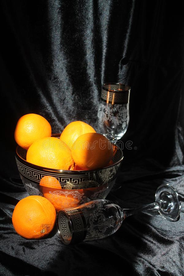 Holiday dessert. Beautiful crystal shine wine glasses with golden rings on tops with sweet juicy orange fruits  for decoration on holiday stock photos