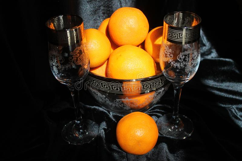 Holiday dessert. Beautiful crystal shine wine glasses with golden rings on tops with sweet juicy orange fruits  for decoration on holiday stock photography