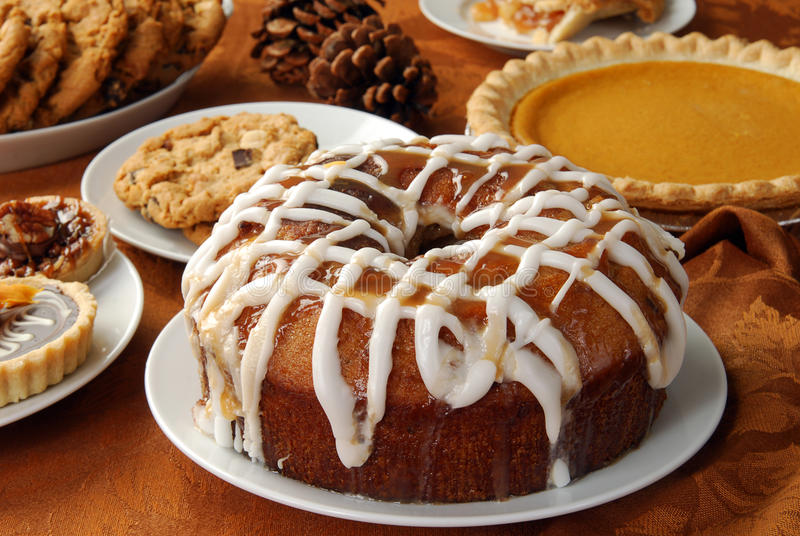 Holiday desserts. An apple bundt cake with caramel glaze and frosting and other holiday treats royalty free stock image
