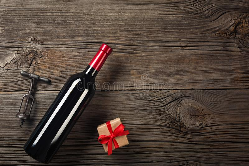 Holiday Dinner setting with red wine and gift on rustic wood in flat stock photos