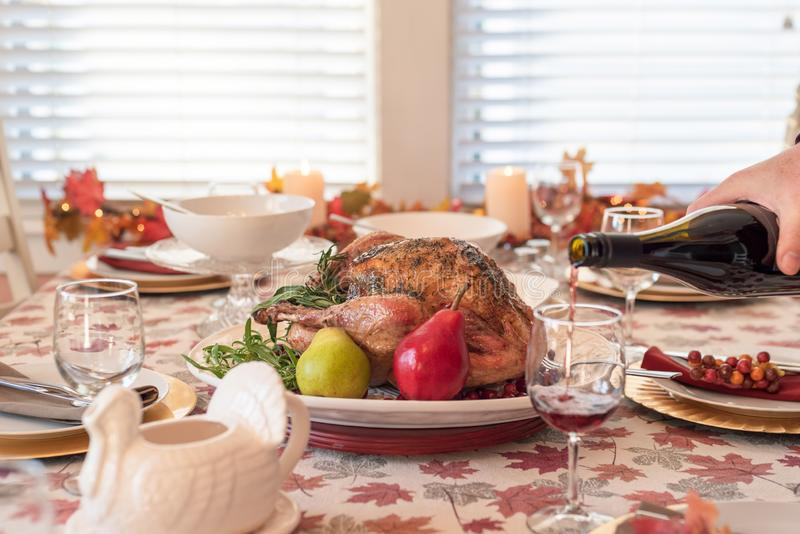 Holiday dinner table with roasted turkey, man pouring red wine in the foreground. Thanksgiving food royalty free stock photography