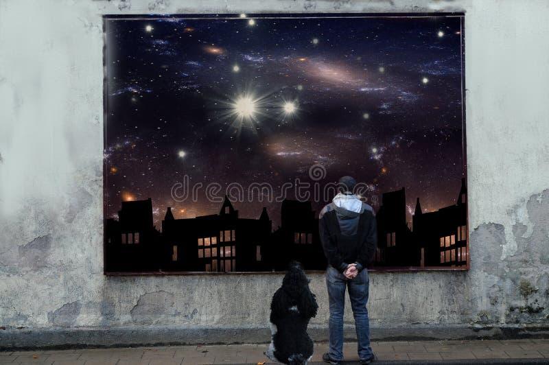 Holiday dreams. Man and dog looking at billboard and dreaming of holidays under the stars
