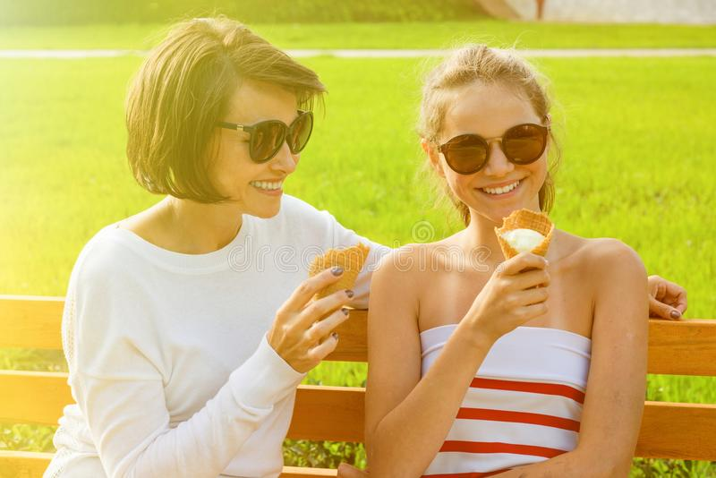 Happy young mother and cute daughter of a teenager in a city park eating ice cream, talking and laughing stock photo