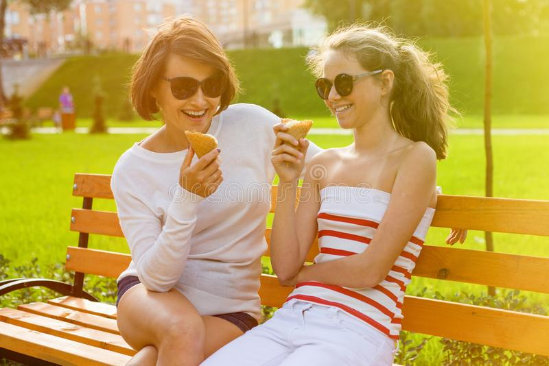 Holiday with the family. Happy young mother and cute daughter of a teenager in a city park eating ice cream, talking and laughing royalty free stock photography