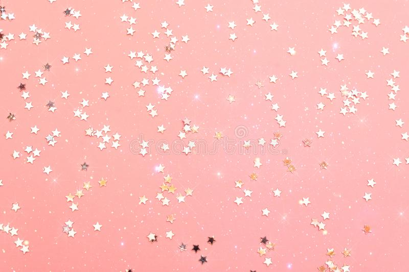 Holiday festive glitter background with pattern from scattered sparkling golden silver stars on pink backdrop. New Years Christmas royalty free stock images