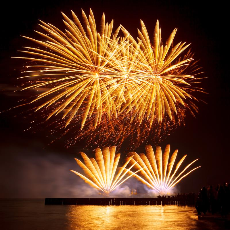 Holiday fireworks of golden color on a black sky background royalty free stock images