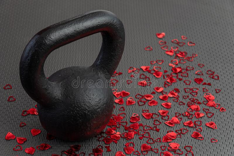 Holiday fitness, black kettlebell, with red heart confetti, on a black gym floor royalty free stock photos