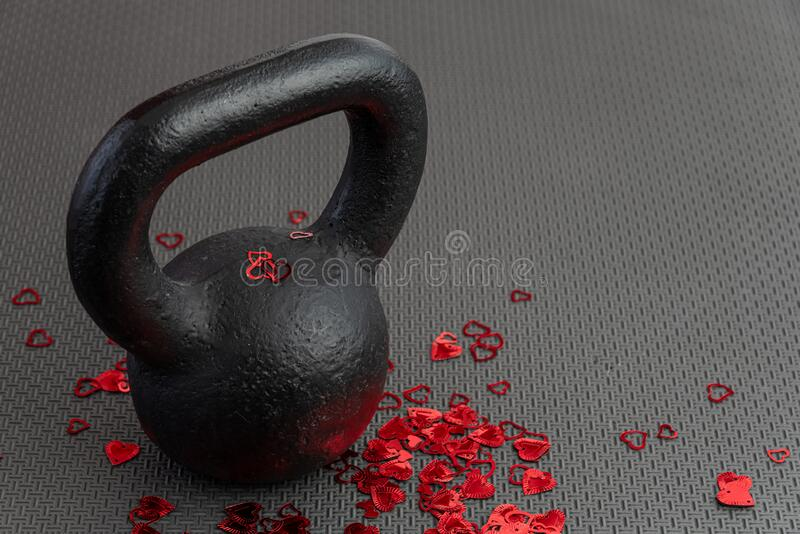 Holiday fitness, black kettlebell, with red heart confetti, on a black gym floor royalty free stock photography