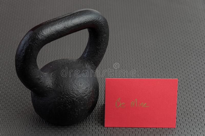 Holiday fitness, black kettlebell, with a red valentine card, on a black gym floor royalty free stock photos