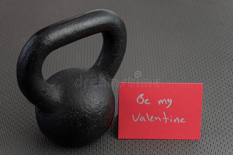 Holiday fitness, black kettlebell, with a red valentine card, on a black gym floor stock photography