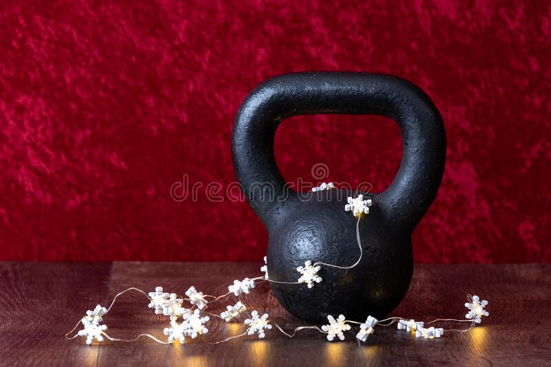 Holiday fitness, black kettlebell with white snowflake twinkle lights, against a red background royalty free stock photos