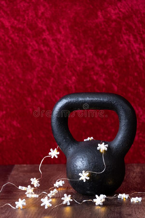 Holiday fitness, black kettlebell with white snowflake twinkle lights, against a red background stock image