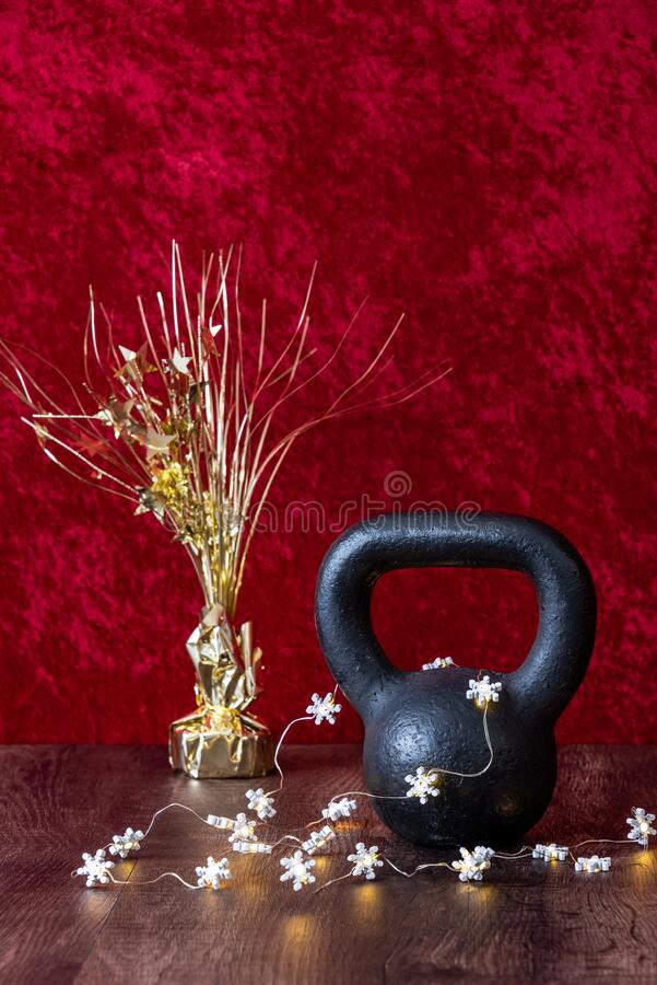 Holiday fitness, black kettlebell with white snowflake twinkle lights, gold decoration with stars against a red background royalty free stock photography