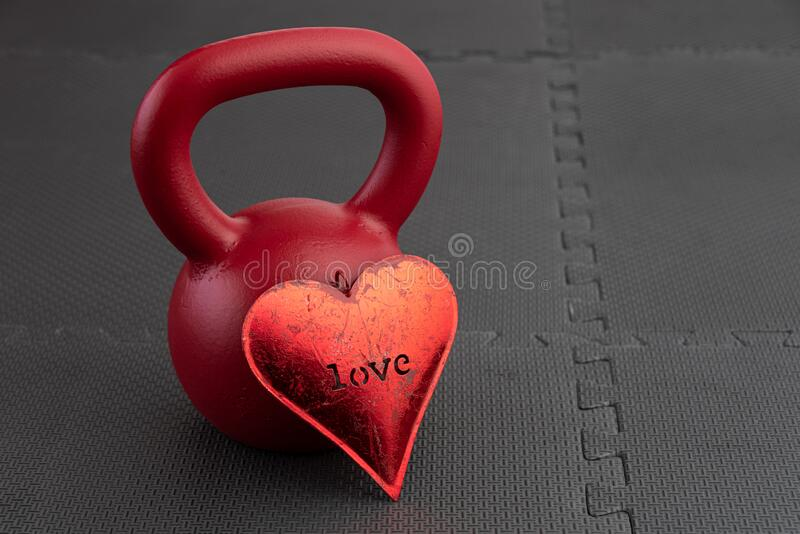 Holiday fitness, red kettlebell, with a metal red heart, on a black gym floor royalty free stock photo