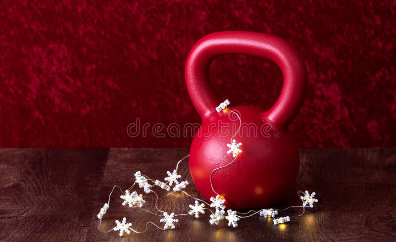 Holiday fitness, red kettlebell with white snowflake twinkle lights, against a red background stock photography