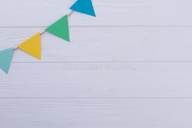 Holiday flags garland on white wooden background. royalty free stock photos