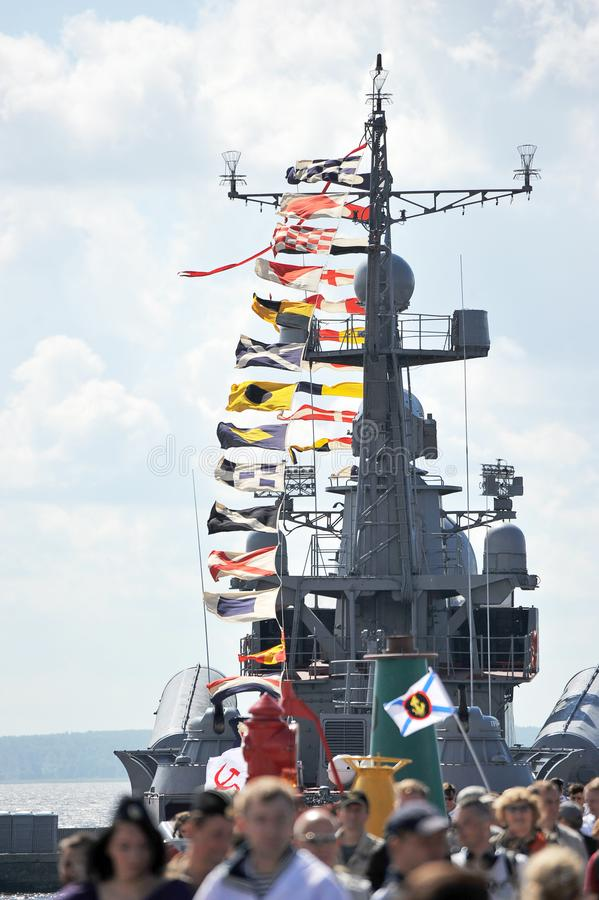 Holiday flags on Russian warship and the people on holiday. In the foreground stock photo